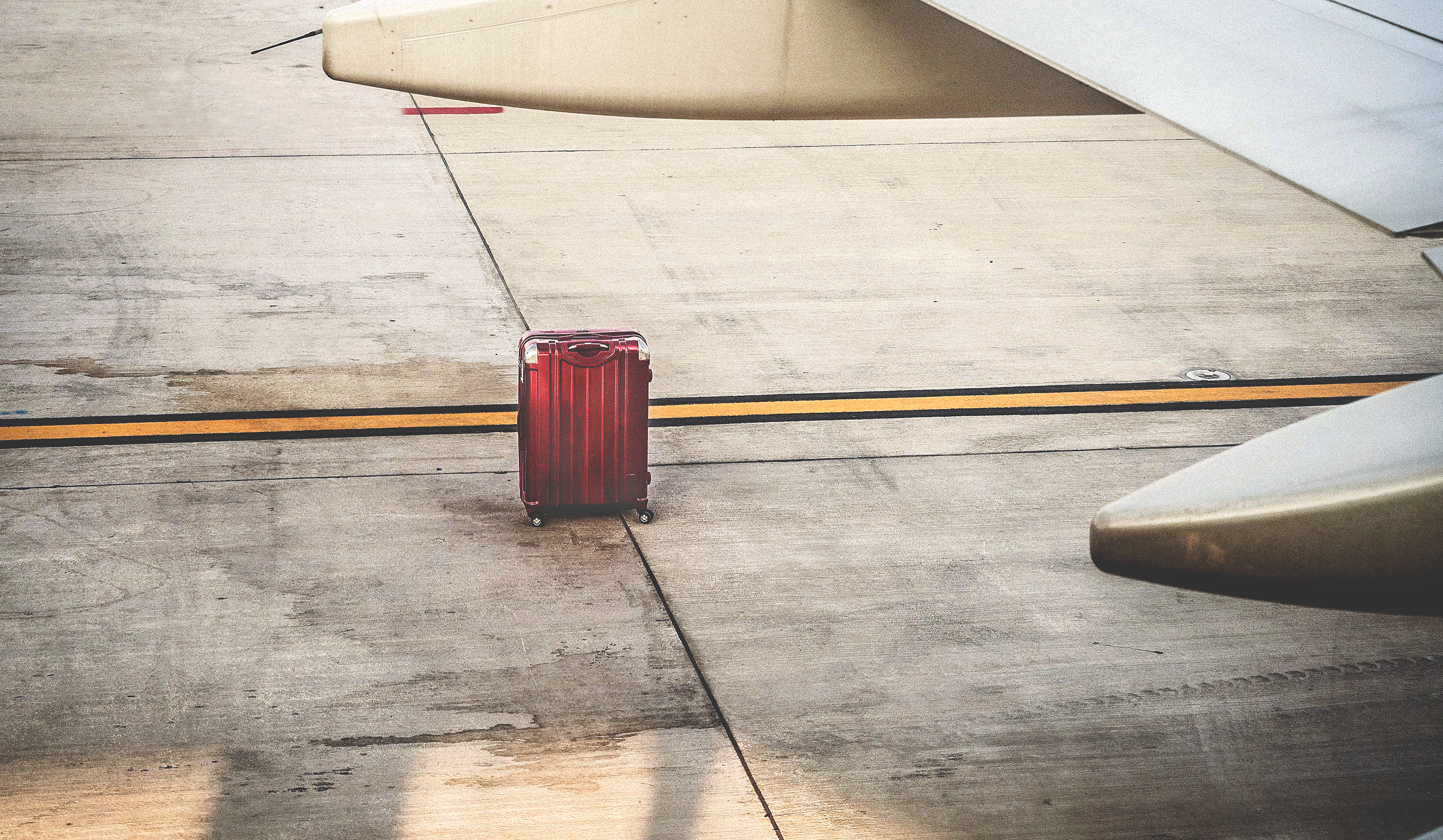 A single red suitcase on the tarmac near an airplane.>From Media Library>From Media Library>From Media Library>From Media Library>From Media Library>From Media Library>From Media Library>From Media Library