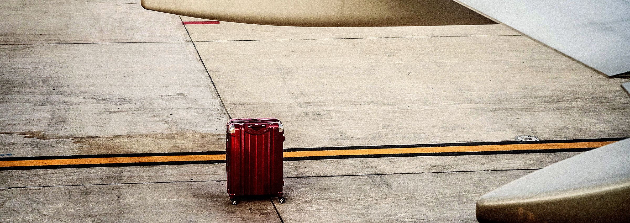 A single red suitcase on the tarmac near an airplane.>From Media Library>From Media Library>From Media Library>From Media Library>From Media Library>From Media Library>From Media Library>From Media Library>From Media Library>From Media Library>From Media Library