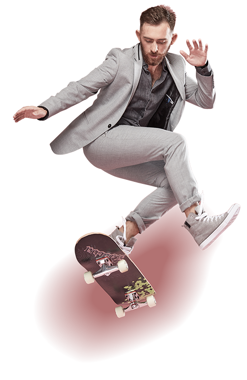 Male in suit doing a skateboarding trick.