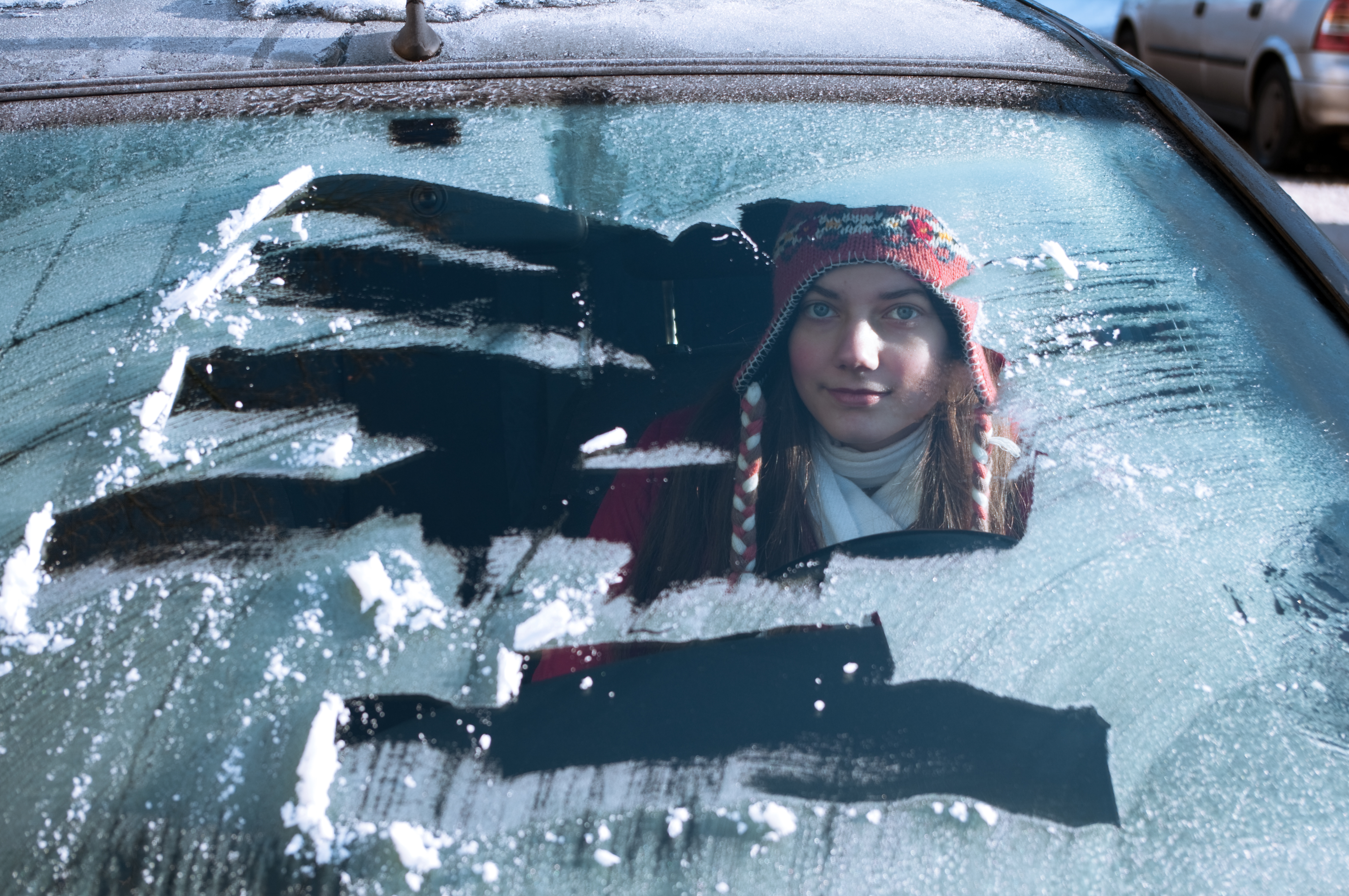 Young female driving a car, but did not scrap all of the snow off of the windshield.
